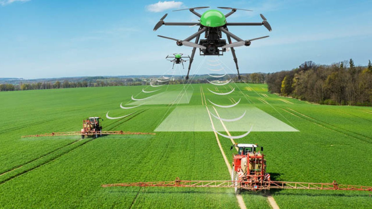 Drone hovering over grass filled field whilst sprayers spray the field with pesticides